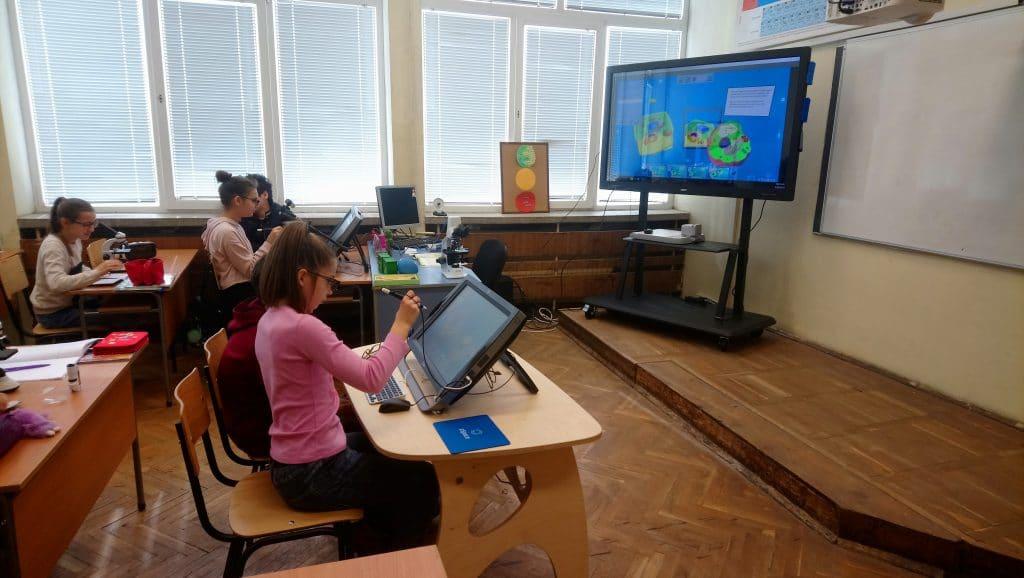 Ученици работят в класна стая с интерактивен дисплей и zSpace